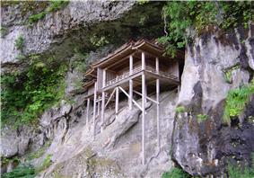 A wooden structure on a cliff face supported by long wooden poles.