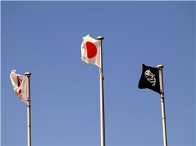 Three flags fly in the sky.