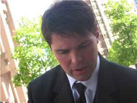 Jágr, a caucasian man with short, brown hair, has his head turned down slightly and is wearing a black suit and tie with a white dress shirt.
