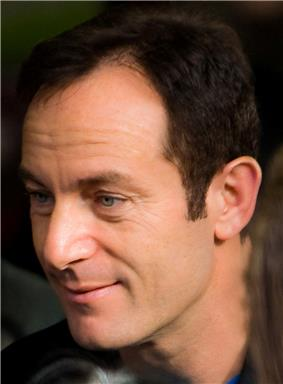 A man with dark brown hair and gray eyes is looking forward and smiling.