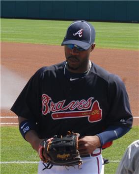Jason Heyward on a grassy field, wearing a Braves uniform and holding a baseball glove