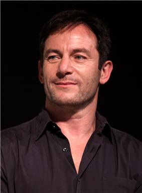 A man with short black hair and a black shirt, who is smiling.