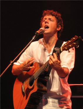 A curly haired man, strumming a guitar and wearing a white shirt.
