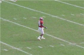American football player waiting to field a punt on a green field.