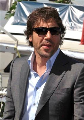 A picture of a Spanish man with sunglasses. He is wearing a greay coat over an unbuttoned light blue collared shirt.