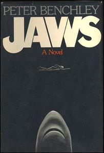 A black cover depicting a woman swimming and a shark coming towards her from below. Atop the cover is written