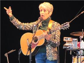 Baez holds guitar, in blue jeans, brown mock turtleneck, patterned jacket, black backdrop, talking and gesturing