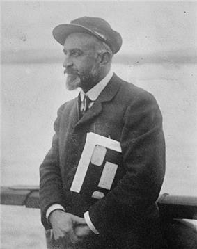 An older bearded man with a hat wearing a tie and coat. He is keeping a pile of papers or documents under his arm.