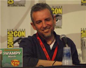 A Caucasian man in his forties, seated at a conference, with a microphone in front of him. He has a pleasant square face, deep-set eyes, greyish hair and a brown beard with clean-shaved cheeks and upper-lip. He is casually dressed, relaxed and smiling. Square signs are posted on the wall behind him, bearing the name COMIC-CON in big bright yellow letters around a drawn eye and eyebrow.