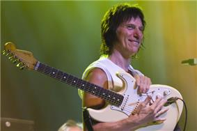 A man wearing a sleeveless white shirt holding a white guitar