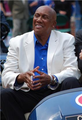 A middle-aged black man sitting. He is bald, smiling, and wearing a blue shirt with a white coat.