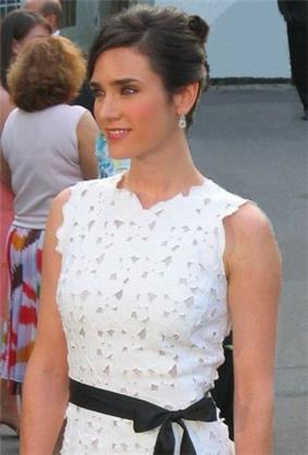 A brown haired woman, wearing a white dress with small flowers detail and a black ribbon in her hips. She is also wearing pendants. Behind her there is a woman dress with a white shirt and a white skirt with big flowers details.