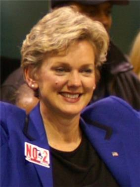 A middle-aged woman with blond hair, smiling