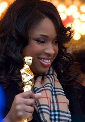 Headshot of an African-American female in her late twenties holding her Oscar statuette