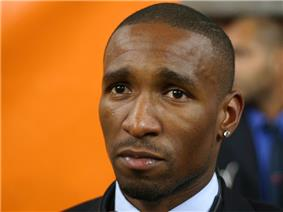 A black man with very short hair and a diamond earring in his left ear