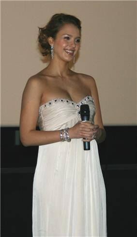 Smiling young woman in strapless white dress, holding a microphone.