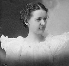 Head and shoulders of a woman, about age 20. Her dark hair is tightly coiffed and parted in the middle near her forehead. The ruffles of her white dress extend like stubby wings from her shoulders.