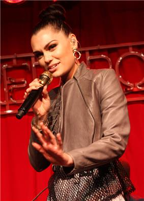 Jessie J with her hair in a bun sings into a microphone before a red curtain