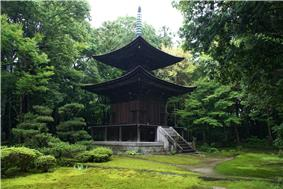Two-storied wooden pagoda with a square lower and a round upper floor.
