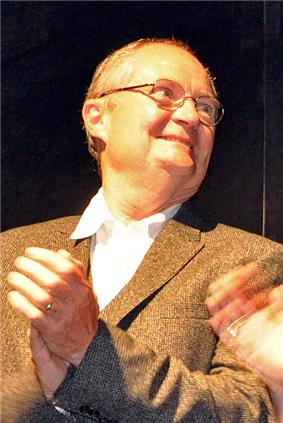 A portrait of a bespectacled, balding male in his late fifites. He is wearing a brown coat over a white collared shirt.