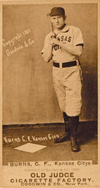 A baseball player is standing, holding a baseball bat.