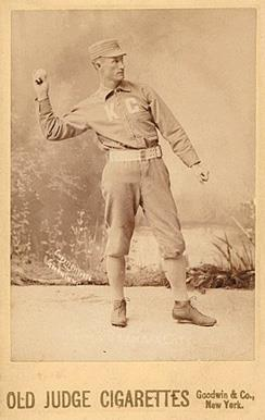 A baseball player is standing in his uniform, with his arm extended in the act of throwing a baseball.