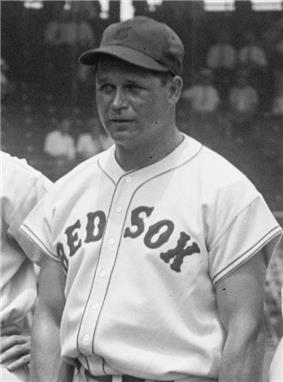 A man is pictured from his belt up looking to the left of the camera. His button-down baseball jersey says