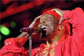A man in red clothing singing into a microphone.