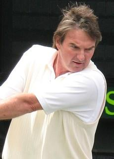 A brown-haired man dressed in a white shirt swings a two-handed backhand