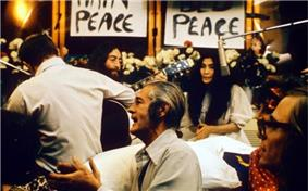 Lennon and Ono sit in front of flowers and placards bearing the word
