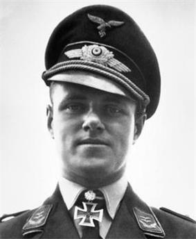 The head and shoulders of a young man. He wears a peaked cap and a military uniform with an Iron Cross displayed at the front of his shirt collar. His facial expression is a determined; his eyes are looking into the camera.