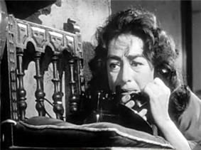 Facial shot of a dishevelled Crawford on the telephone.