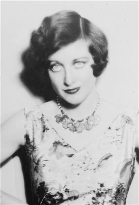 Upper body studio shot of a young Crawford in a sleeveless dress, with accented eye make-up, coiffed hair. She is staring into the camera.