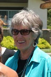 Head shot of a short-haired woman in sunglasses.