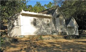 Photograph of the Joaquin Miller House. A small house on a gradual incline, elevated by brick foundation, surrounded by trees.
