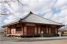 Wooden building with slightly raised floor, open veranda, red beams, white walls and a pyramid shaped roof.