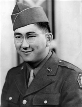 Head and shoulders of a smiling young man with dimples and round wire-framed glasses wearing a garrison cap and a military jacket over a shirt and tie.