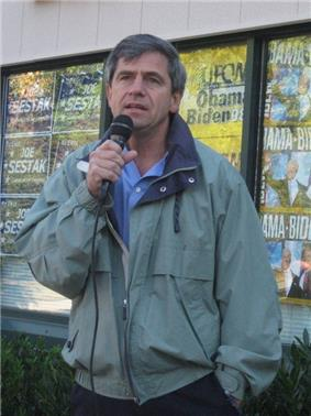 A gray-haired man wearing a green jacket speaks into a microphone outside in front of a building, with campaign signs that read
