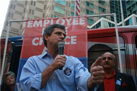 A gray-haired man wearing a blue shirt and black campaign button speaks into a microphone at an outside political rally. A man and woman stand behind him, and a banner reading