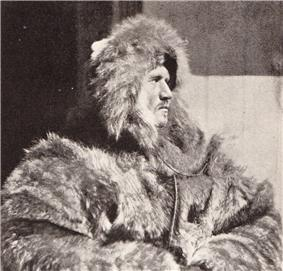 Head and upper body of a man, facing right. He is dressed in heavy fur clothing including a hat which conceals much of his face, although the profile is clear