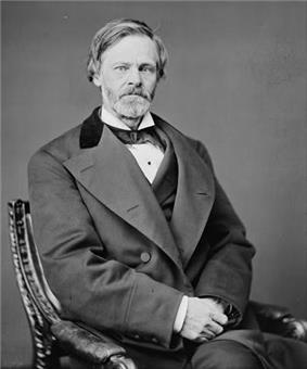 A 19th-century American gentleman is photographed in black and white, sitting in an ornate chair and looking into the camera. His sandy-coloured hair is somewhat longer on the top than might be expected, and he wears a full beard. He is attired in a dark suit and white shirt.