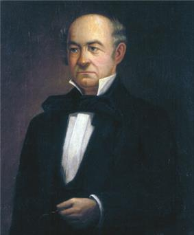 A bald man wearing a white shirt and black jacket, holding glasses in his left hand