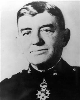 A black and white image of John A. Lejeune, a white male in his Marine Corps dress blue uniform. A medal is clearly visible around his neck. He is not wearing a hat.