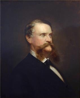 A man with receding brown hair and an extremely long, bushy mustache wearing a white shirt, black tie, and black jacket