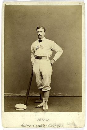 A baseball player is shown standing in his baseball uniform, leaning on the end of a baseball bat.
