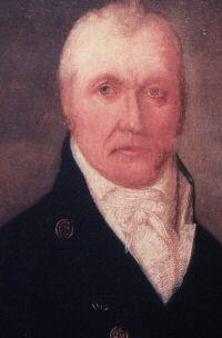 Portrait of the head of man wearing black coat and a white scarf around his neck.