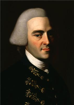 Half-length portrait of a man with a hint of a smile. His handsome features suggests that he is in his 30s, although he wears an off-white wig in the style of an English gentleman that makes him appear older. His dark suit has fancy embroidery.