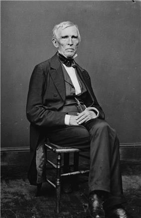 A man with gray hair wearing a black suit and white shirt, sitting with his hands folded