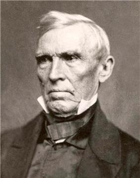 A white-haired man wearing a black jacket, gray tie and vest, and white, high-collared shirt