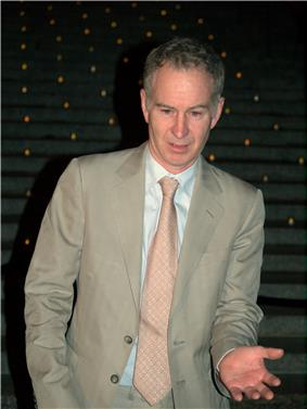 A grey-haired man in a grey suit and tie raises his left hand